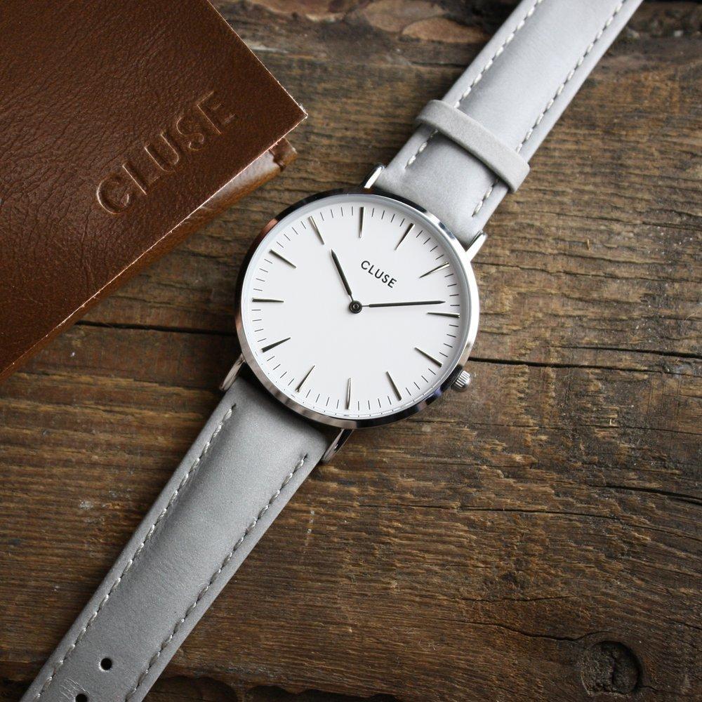 Klasyczny, damski zegarek Cluse CL18215 Silver White/Grey na skórzanym pasku w szarym kolorze z okrągłą, srebrną kopertą z mosiądzu oraz analogową minimalistyczną tarczą w białym kolorze.