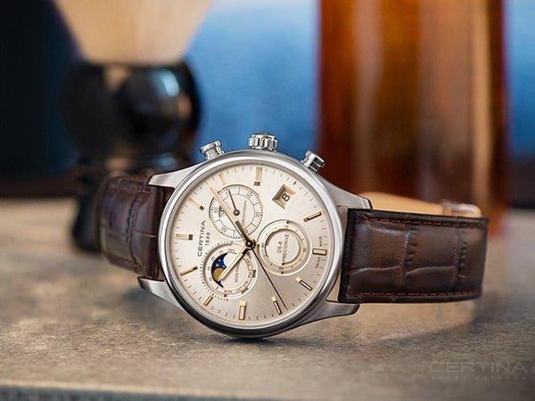 Zegarek Certina na skórzanym brązowym pasku z fazami księżyca na tarczy.