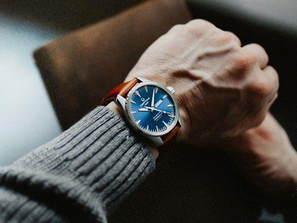 Klasyczny zegarek Certina z niebieską tarczą na brązowym pasku.