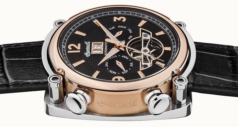 Amerykański, męski zegarek Ingersoll I01102 The Michigan na skórzanym czarnym pasku z kopertą w takich kolorach jak srebro i złoty róż. Tarcza typu open heart jest w czarnym kolorze z ozdobieniami w kolorach złotego różu i srebra.