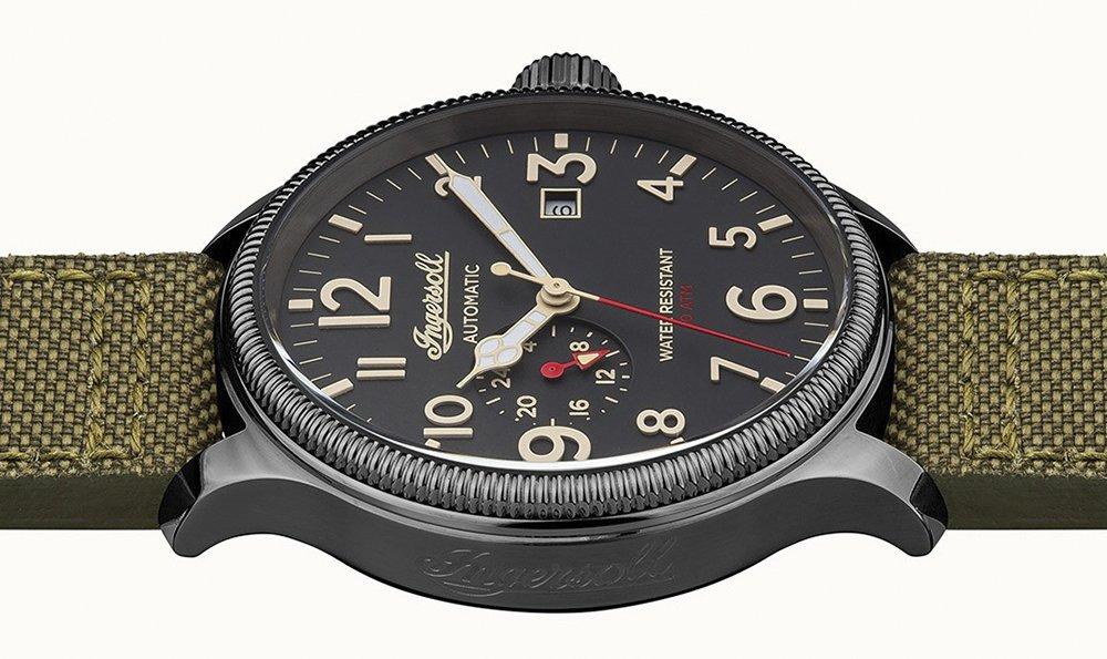 Wodoszczelny, męski zegarek Ingersoll na pasku z naturalnej skóry oraz materiału z stalowa koperta w szarym kolorze. Tarcza zegareka jest w czarnym kolorze z wyraźnymi i łatwymi to przeczytania indeksami.