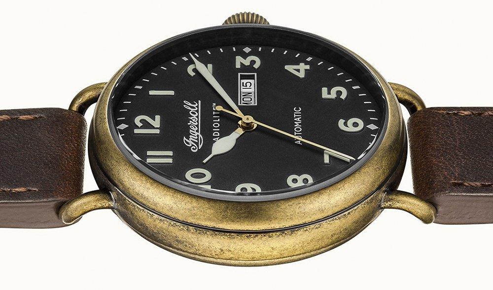 Minimalistyczny, męski zegarek Ingersoll I03403 w stylu retro jest na skórzanym, brązowym pasku oraz złotą, okrągłą kopertą z postarzanym efektem. Tarcza zegarka jest w czarnym kolorze z wyraźnymi indeksami.