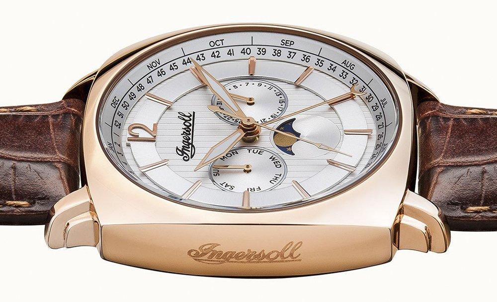 Odkrywczy, męski zegarek Ingersoll I04103 The Columbus na skórzanym pasku w kolorze ciemnego brązu oraz kwadratowej kopercie w kolorze różowego złota. Tarcza zegarka jest w srebrnym kolorze z funkcją faz księżyca oraz kalendarzem.