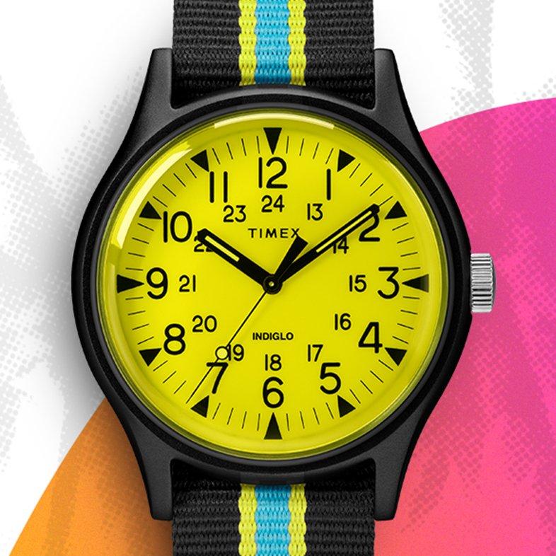 Młodzieżowy zegarek Timex TW2T25700 Aluminum California z mechanizmem kwarcowym i oświetleniem indiglo. Zegarek jest z aluminiową kopertą w srebnrym kolorze i parcianym pasku w czarnym, żółtym oraz niebieskiem kolorze.