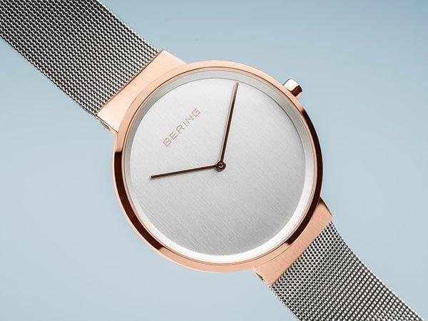 Minimalistyczny zegarek Bering na srebrnej bransolecie mesh z kopertą w kolorze różowego złota.