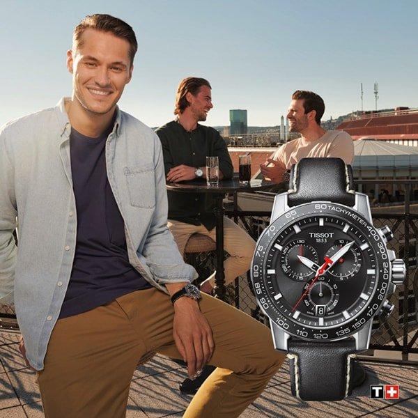 Sportowy zegarek Tissot na czarnym skórzanym pasku z srebrna koperta oraz czerwonymi detalami na czarnej tarczy.