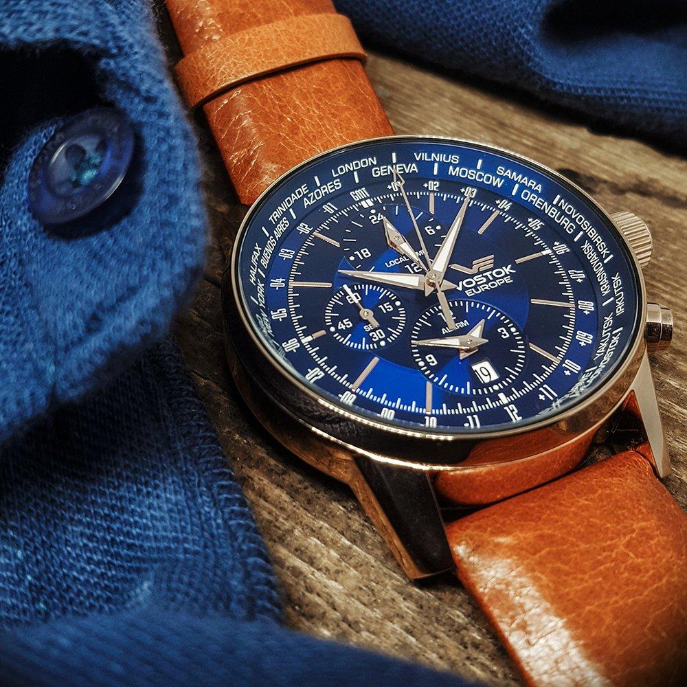 Luksusowy, męski zegarek Vostok Europe YM26-5609256 Limousine Chrono na brązowym skórzanym pasku ze stalową kopertą pokrytą PVD w kolorze różowego złota. Analogowa tarcza w kolorze niebieskim jest podkreślona przez subtarcze w złotym oraz białym kolorze.