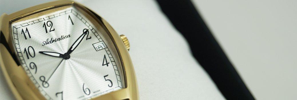 Zegarek Adriatica w stylu artdeco. Bezel zegarka jest złoty a tarcza jest w białym kolorze wykonana gliszowaniem.
