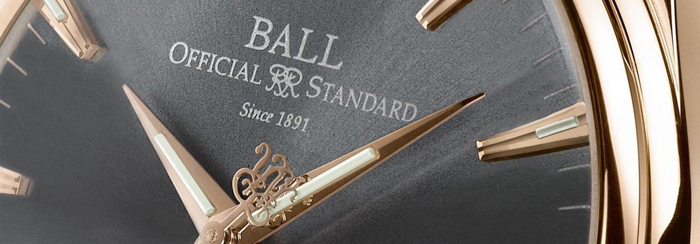 Elegancki zegarek Ball z szarą, minimalistyczną tarczą oraz kopertą i wskazówkami w kolorze różowego złota.