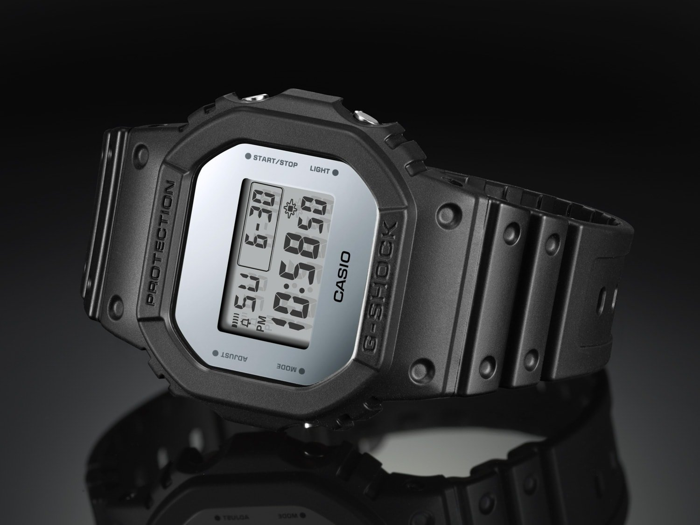 Limitowany, męski zegarek G-Shock DW-5600BBMA-1ER Metallic Mirror Face na pasku z tworzywa sztucznego w czarnym kolorze z kopertą o niestandardowym kształcie z tworzywa sztucznego. Cyfrowa tarcza ma srebrny kolor.