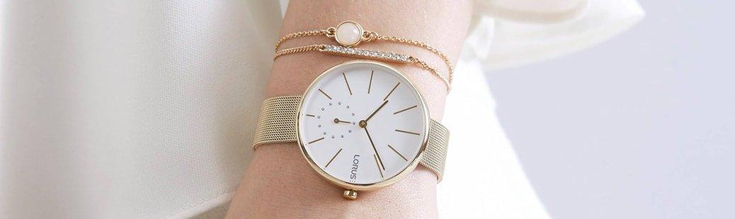 Klasyczny, damski zegarek Lorus na stalowej bransolecie w złotym kolorze w stylu mesh. Koperta zegarka jest w złotym kolorze ze stali a analogowa tarcza jest w białym kolorze z złotymi indeksami w postaci cieniutkich kresek.