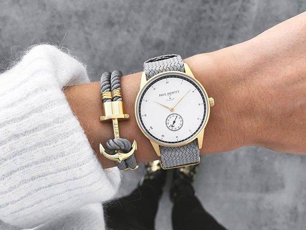 Stylowy zegarek Paul Hewitt na szarym plecionym pasku ze złotą kopertą oraz białą tarczą z subtarczą na godzinie szóstej
