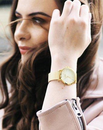 Złoty zegarek Timex z analogową tarczą.