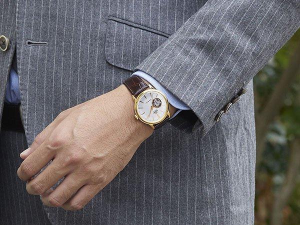 Elegancki zegarek Orient na brązowym pasku ze złotą koperta oraz białą tarczą w stylu open-heart.