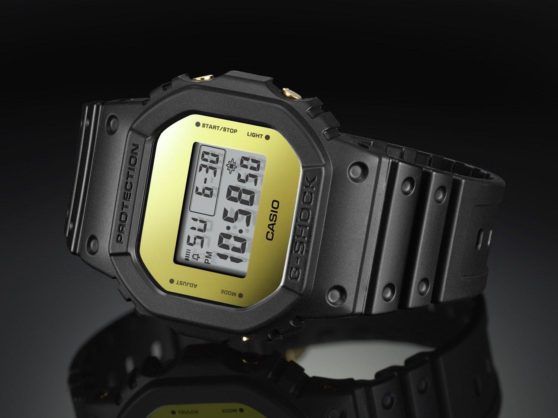 Sportowy, męski zegarek G-Shock DW-5600BBMB-1ER Metallic Mirror Face na pasku z tworzywa sztucznego w czarnym kolorze z kopertą o niestandardowym kształcie z tworzywa sztucznego. Cyfrowa tarcza ma złoty kolor.
