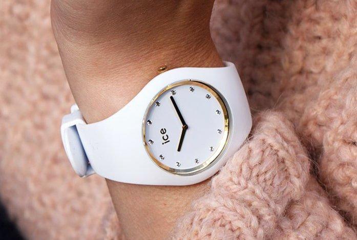 Delikatny, damski zegarek ICE Watch ICE.016296 ICE Cosmos na białym silikonowym pasku posiada białą tarczę ozdobioną srebrnymi kryształkami Swarovskiego na indeksach oraz złotym bezelem i wskazówkami.