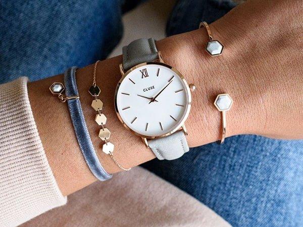Damski zegarek Cluse na jasnym pasku z białą tarczą.