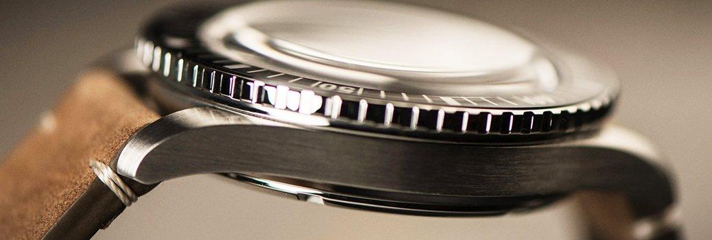 Srebrna koperta zegarka na brązowym zamszowym pasku.