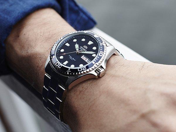 Niezawodny zegarek diver marki Orient na srebrnej bransolecie  z czarną tarczą oraz datownikiem.