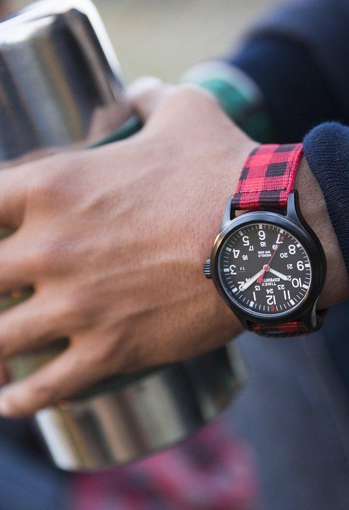 Męski zegarek Timex na parcianym pasku w czerwoną kratkę z czarną kopertą wykonaną z tworzywa sztucznego. Analogowa tarcza zegarka jest w czarnym kolorze z białymi cyferkami jak i wskazówkami.