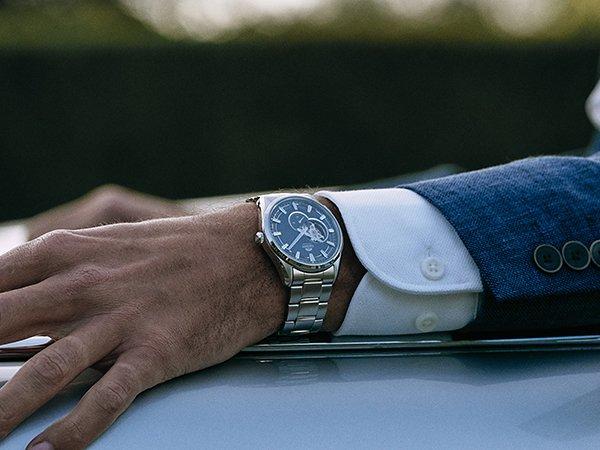 Stylowy zegarek marki Orient na srebrnej bransolecie z ciemną tarczą typu open-heart.