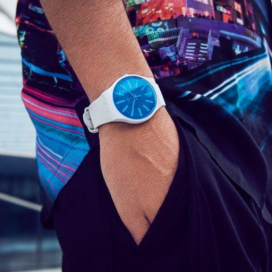 Zegarek Swatch z paskiem z tworzywa sztucznego w białym kolorze z niebieską analogową tarczą.
