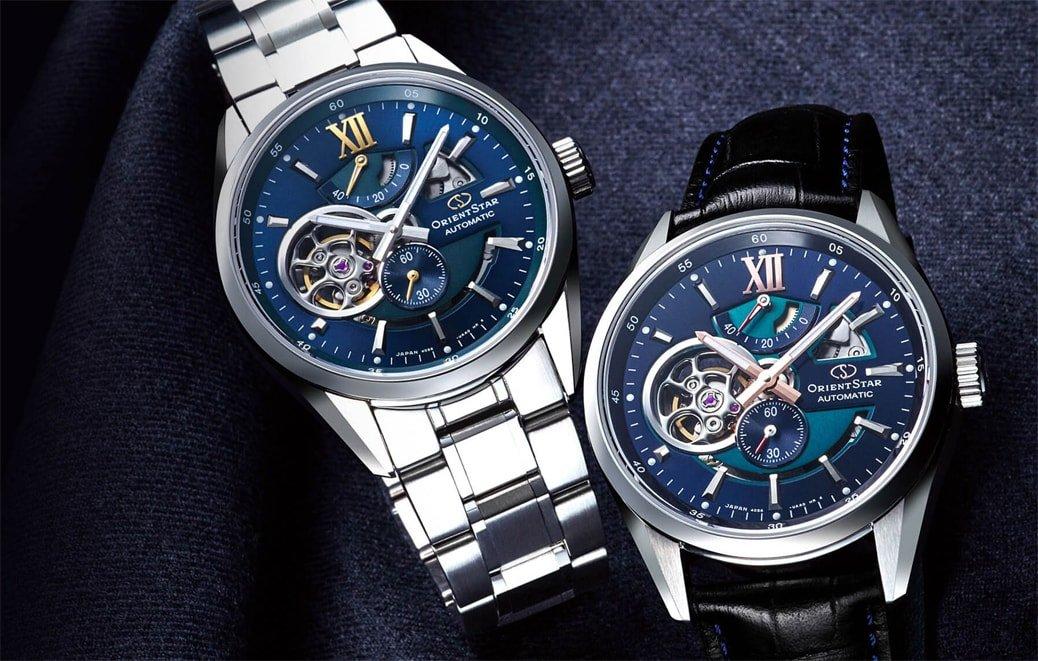 Luksusowe, męskie zegarki Orient Star z mechanizmem automatycznym. Jeden z nich jest na czarnym skórzanym pasku, a drugi na stalowej bransolecie w srebrnym kolorze. Oba zegarki Orient Star mają kopertę z stali w srebrnym kolorze oraz analogową tarczę w stylu open heart w niebieskim kolorze.