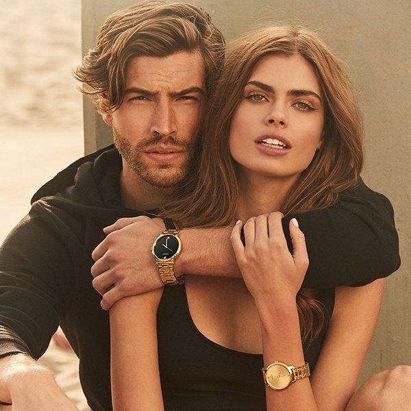 Elegancki męski zegarek Guess z klasyczną stylistyką w złotym kolorze z dwoma kamieniami na godzinie dwunastej oraz szóstej.