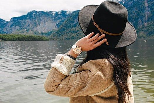 Atrakcyjny zegarek Swatch z bezelem w kolorze różowego złota na białym skórzanym pasku z odkrytym mechanizmem.