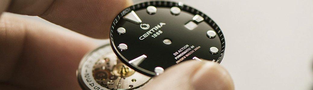 Czarna tarcza zegarka Certina z białymi indeksami.