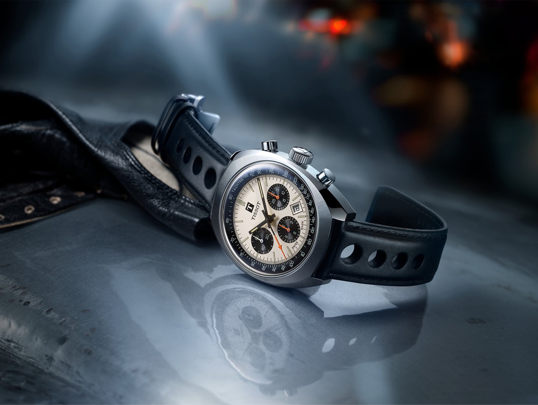 Luksusowy, męski zegarek Tissot T124.427.16.031.00 HERITAGE 1973 na skórzanym pasku w czarnym kolorze z owalną kopertą wykonaną ze stali w srebrnym kolorze. Tarcza zegarka jest w beżowym kolorze z trzema subtarczami oraz datownikiem pomiedzy godziną czwartą a piątą.