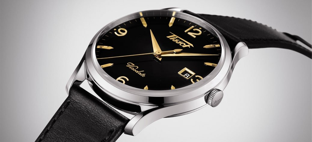 Luksusowy, męski zegarek Tissot T118.410.16.057.01 HERITAGE VISODATE na skórzanym tłoczonym pasku w kolorze czarnym oraz kopercie ze stali w srebrnym kolorze. Tarcza zegraka jest w czarnym kolorze ze złotymi indeksami oraz wskazówkami.