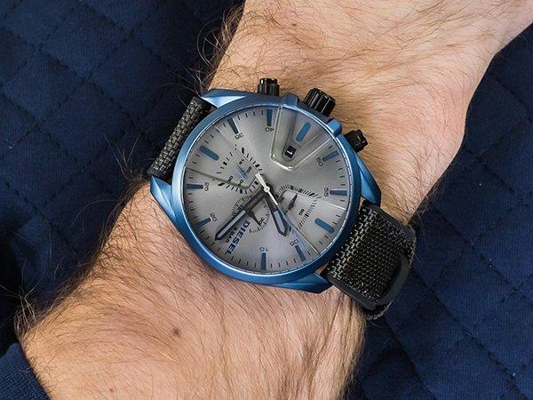 Orginalny zegarek Diesel na parcianym pasku z niebieską kopertą oraz srebrną tarczą dla osób leworęcznych.