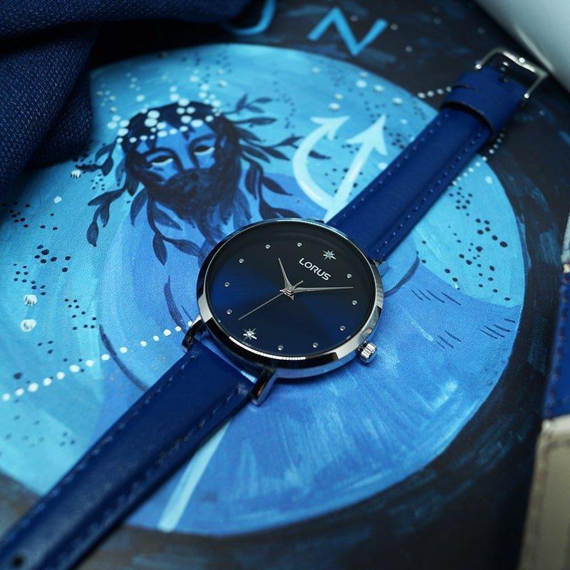 Klasyczny zegarek Lorus na skórzanym granatowym pasku z srebrną kopertą oraz błyszczącą granatową tarczą. Tarcza przyozdobiona jest dwoma gwiazdkami na godzinach jakich jak szósta oraz dwunasta.