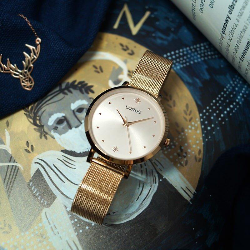 Klasyczny zegarek Lorus na złotej bransolecie typu mesh z złotą kopertą oraz tarczą w tym samym kolorze. Tarcza przyozdobiona jest dwoma gwiazdkami na godzinach jakich jak szósta oraz dwunasta.