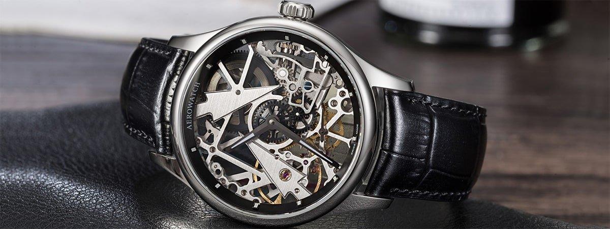 Niezwykły zegarek Aerowatch z widocznym mechanizmem na skórzanym, czarnym pasku.