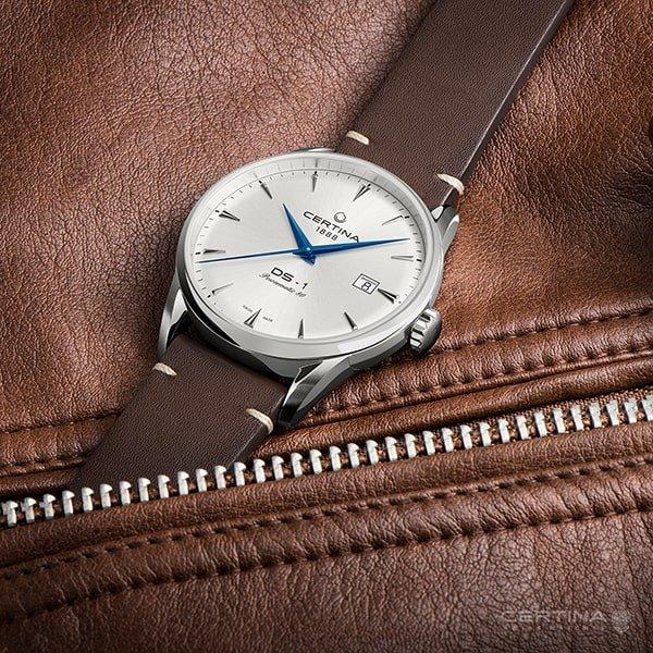 Klasyczny zegarek Certina DS-1 na brązowym pasku z srebrną tarczą jak i kopertą.