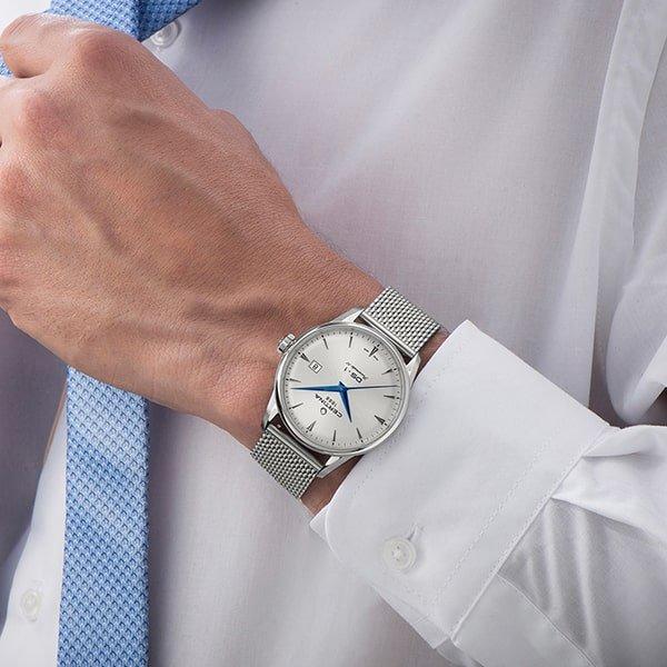 Srebrny zegarek Certina DS-1 na bransolecie mesh z niebieskimi wskazówkami na tarczy.
