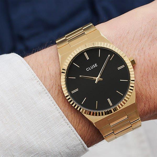 Zegarek Cluse na złotej bransolecie z czarną tarczą.