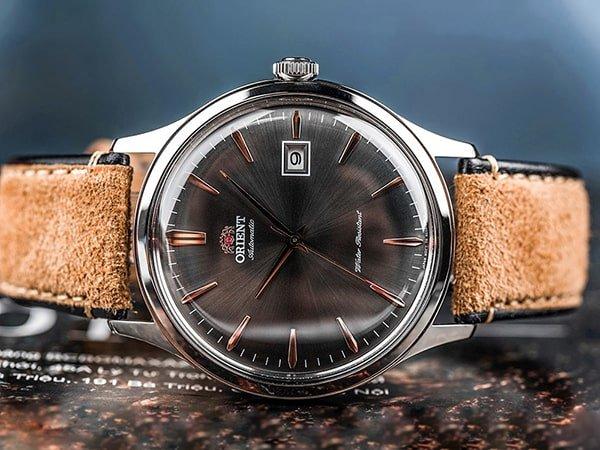 Japoński zegarek marki Orient na brązowym pasku.