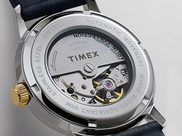 Zegarek Timex z widocznym mechanizmem na kopercie, na niebieskim pasku.