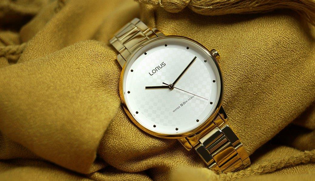 Zegarek Lorus na złotej bransolecie z szachownicą na tarczy. Cyferblaty zostały utrzymane są w monochromatycznej kolorystyce.