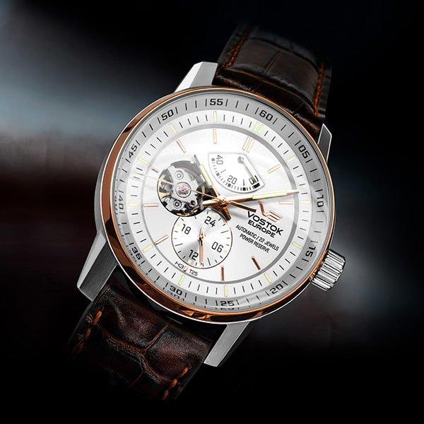 Elegancki zegarek Vostok Europe na skórzanym brązowym pasku z białą tarczą typu open-heart.