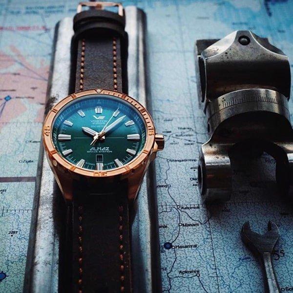 Niepowtarzalny zegarek Vostok Europe na brązowym skórzanym pasku z zieloną tarczą oraz bezelem w miedzianym kolorze.