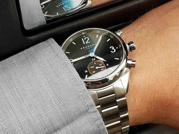 Elegancki zegarek Kronaby na srebrnej bransolecie z czarną tarczą.